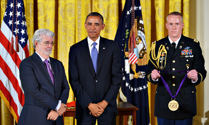 US President Barack Obama stands next to 2012 National Medal of Arts receipent director George Lucas(L) while the citation is read during a ceremony in the East Room of the White House on July 10, 2013 in Washington, DC. — AFP Photo