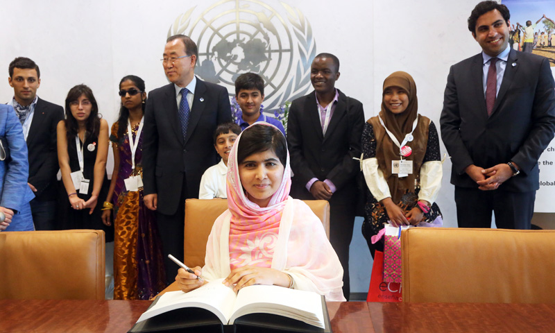 Malala Yousafzai signs United Nations Secretary-General Ban Ki-moon's guest books at United Nations headquarters. -Photo by AP