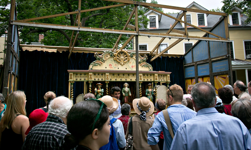 Visitors gather around a 1910 pipe organ to listen as music is played during the press preview for the Fete Paradiso carnival on Governors Island, New York. — AP Photo