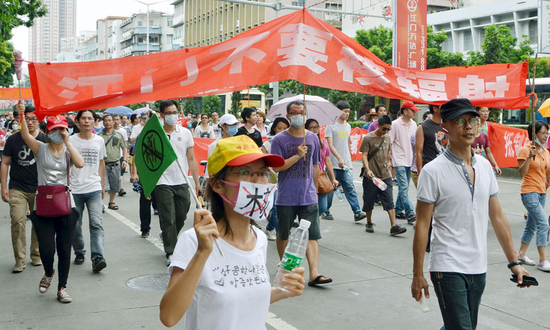 In this Friday, July 12, 2013, photo, protesters who oppose the uranium processing plan in Heshan, parade through a street in Jiangmen, China. – AP Photo