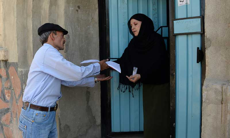 In this photograph taken on June 11, 2013, Afghan postman Mohammad Rahim delivers letters to a resident in the Kart-i-Sakhi neighbourhood of Kabul. — Photo by AFP