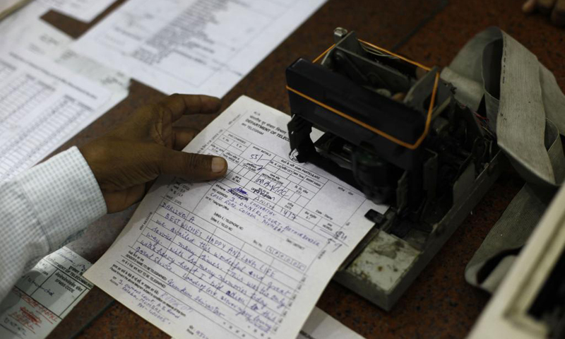 An Indian telegraph employee processes a telegram on the last day of the 163-year-old service at the central telegraph office in Mumbai, India, Sunday, July 14, 2013. Sunday night, the state-run telecommunications company will send its final telegram, closing down a service that fast became a relic in an age of email, reliable landlines and ubiquitous cellphones. — AP Photo