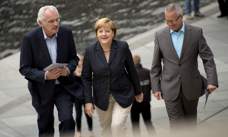 German Chancellor Angela Merkel (C) arrives with her hosts and interviewers Ulrich Deppendorf (L) and Rainald Becker for a summer recess interview with the German public broadcaster ARD. — AFP Photo