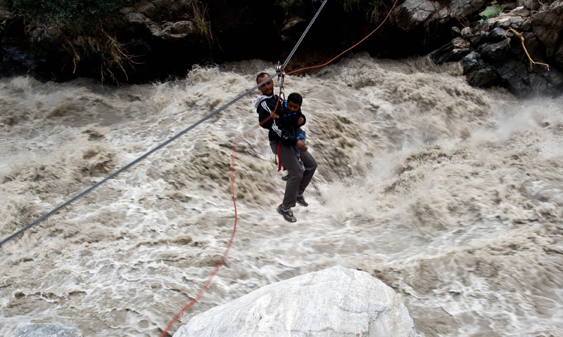 A stranded Indian pilgrim, seen carrying a child, is transported across a river using a rope rescue system by Indo-Tibetan Border Police (ITBP) personnel in Govind Ghat on June 23, 2013.     — Photo by AFP
