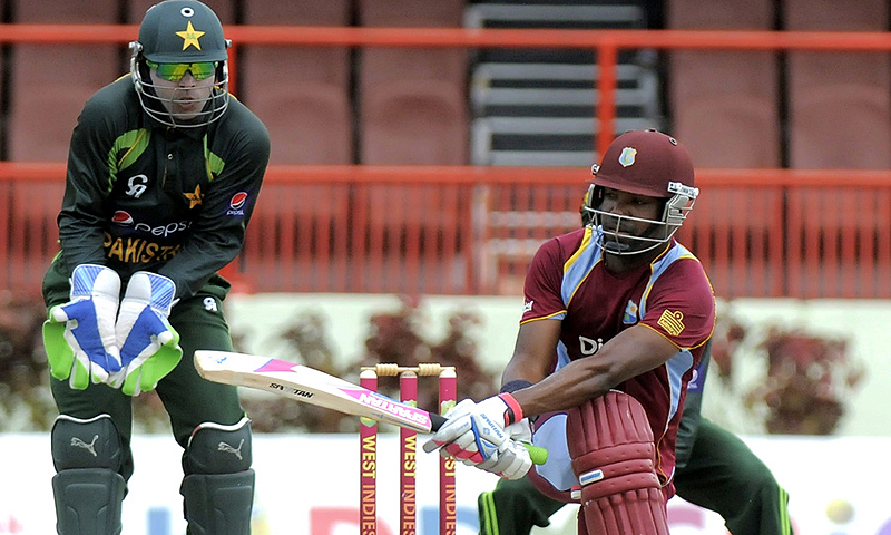 Darren Bravo plays a shot as Umar Akmal looks on. -Photo by AFP