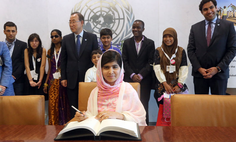 Malala Yousafzai signs United Nations Secretary-General Ban Ki-moon's guest books as Ban Ki-moon, center, and youth delegates look on, Friday, July 12, 2013 at United Nations headquarters. — Photo by AP