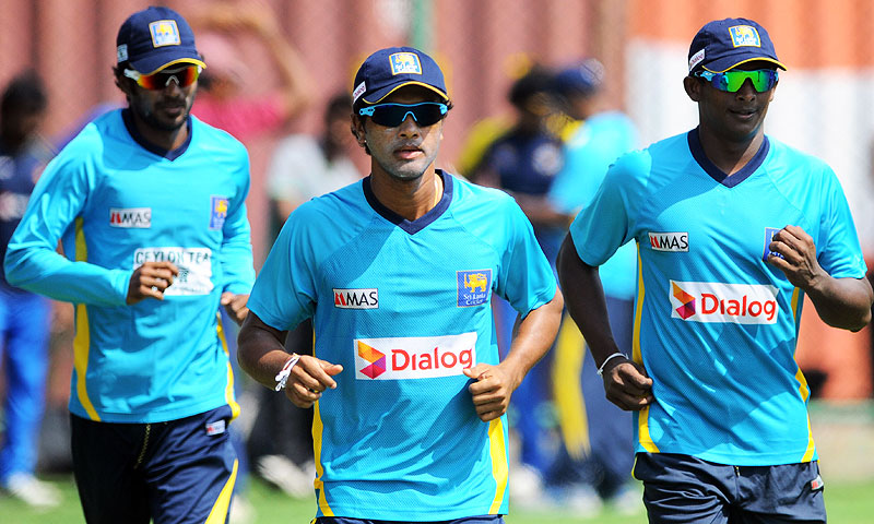 Sri Lankan cricket team captain Dinesh Chandimal (C), Ajantha Mendis (R) and Upul Tharanga (L) warm up during a practice session in Colombo. -Photo by AFP