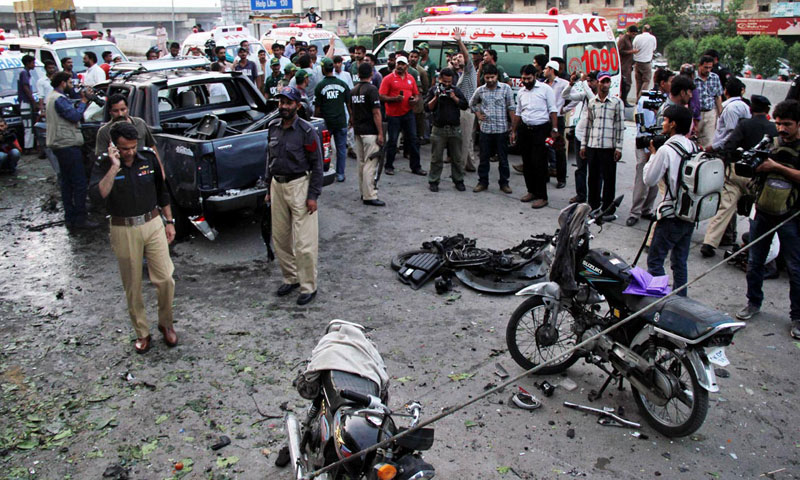 People standing near Metropolitan Commissioner Matanat Ali Khan's vehicle damaged in a bomb attack in Karachi on July 20, 2013.—Photo by Online