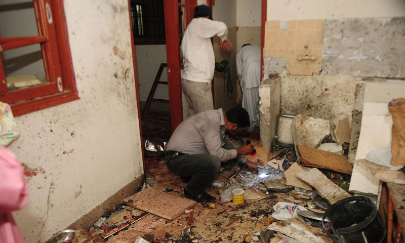 Security personnel collect evidence at the site of a bomb blast in a house in Karachi on July 20, 2013. —AFP Photo