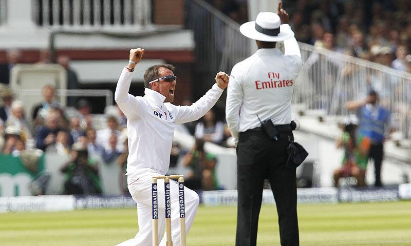 England's Graeme Swann reacts after taking the wicket of Australia's Phillip Hughes. -Photo by AFP