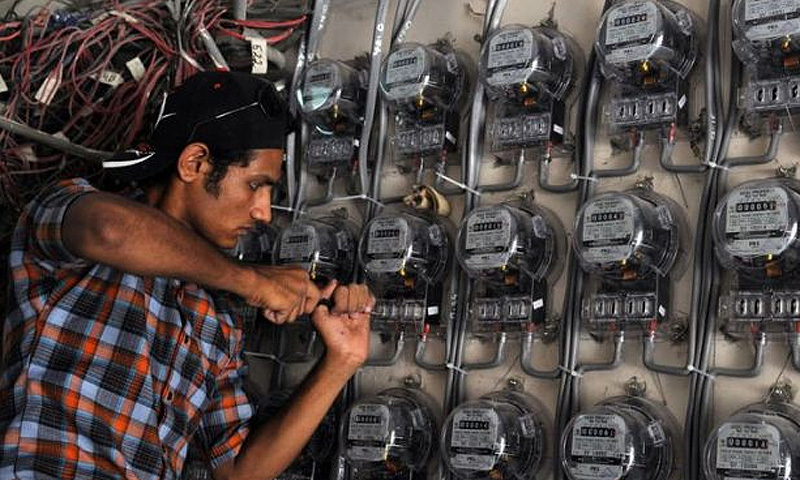 A technician checks electricity meters at a residential building. -File photo by AFP
