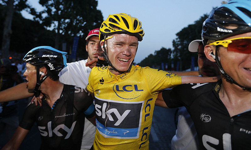 Tour de France 2013 winner Britain's Christopher Froome (C) celebrates with teammates on the Champs-Elysee avenue in Paris. -Photo by AFP