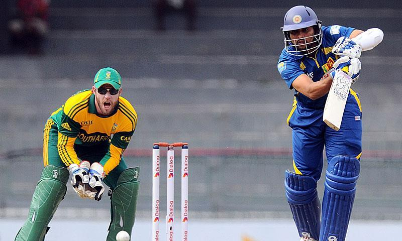Sri Lankan batsman Tillakaratne Dilshan (R) plays a shot while South African wicketkeeper AB de Villiers reacts. -Photo by AFP