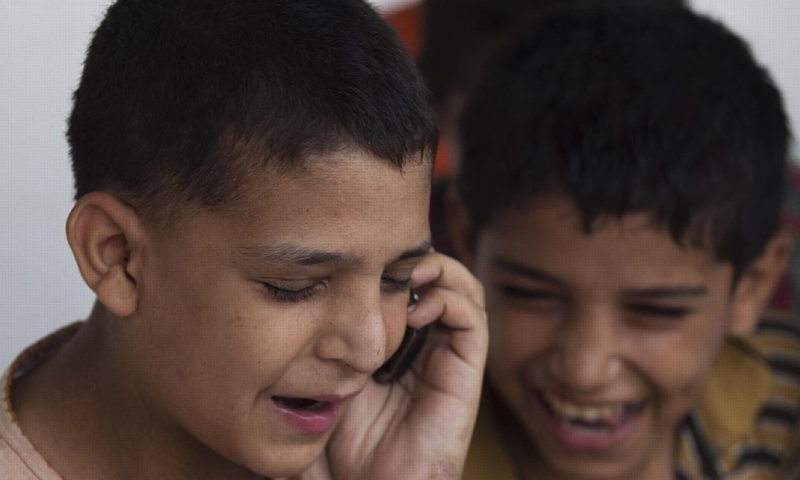 Runaway boy Naveed Khan talks to his father on the phone while waiting to go to his hometown in Peshawar. — AP Photo.