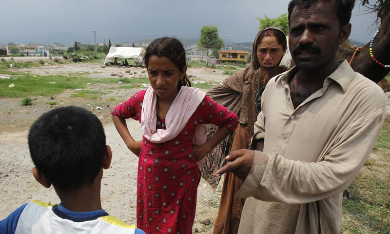 Lost child Shan, who claims to belong to a gypsy family enquires on the whereabouts of his family to a nomad family living in the suburbs of Islamabad. — AP Photo.