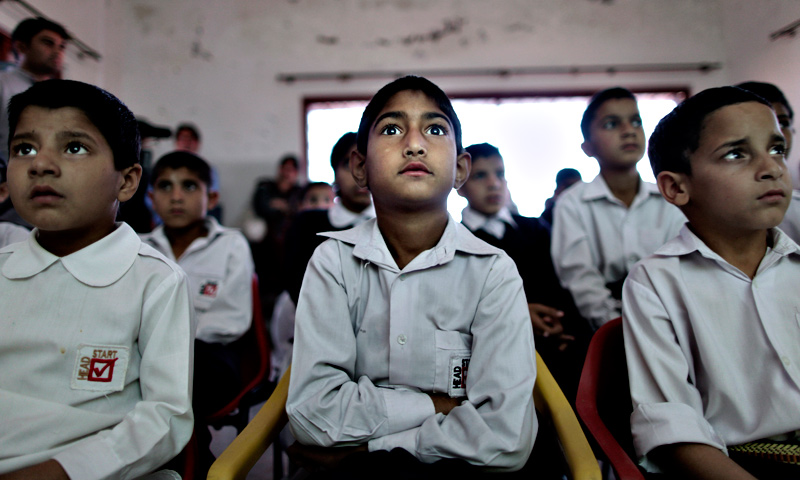 Orphaned children watch an early screening of the first episode of the animate Burka Avenger Series, at an orphanage on the outskirts of Islamabad. — AP Photo