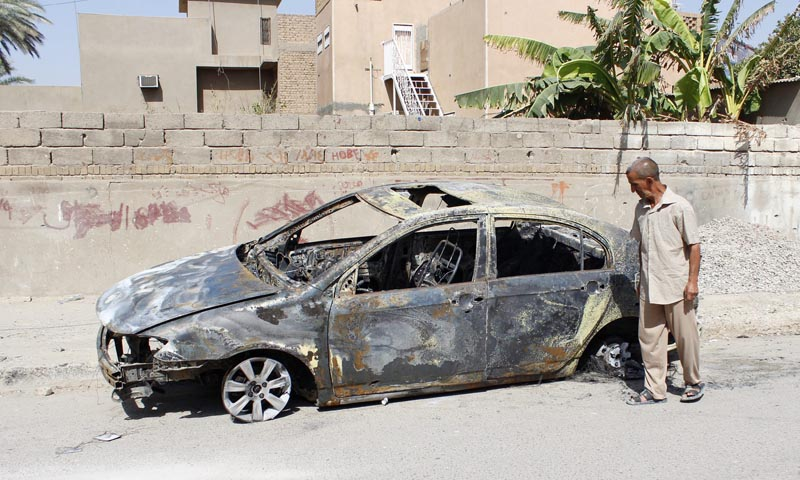 A man looks at a damaged vehicle after a bomb attack last night in Baghdad, July 28, 2013. — Photo by Reuters