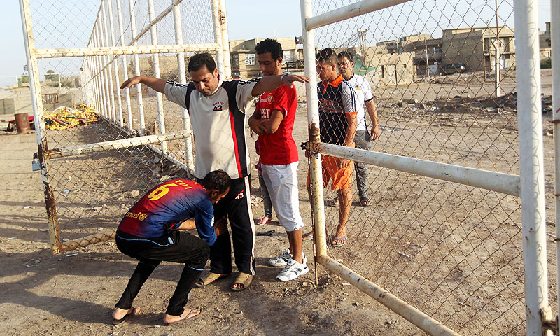 An Iraqi searches a man at the entrance to a football stadium. -Photo by AFP