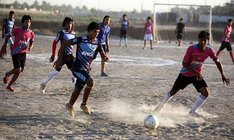 Iraqi youths play football in Baghdad. -Photo by AFP
