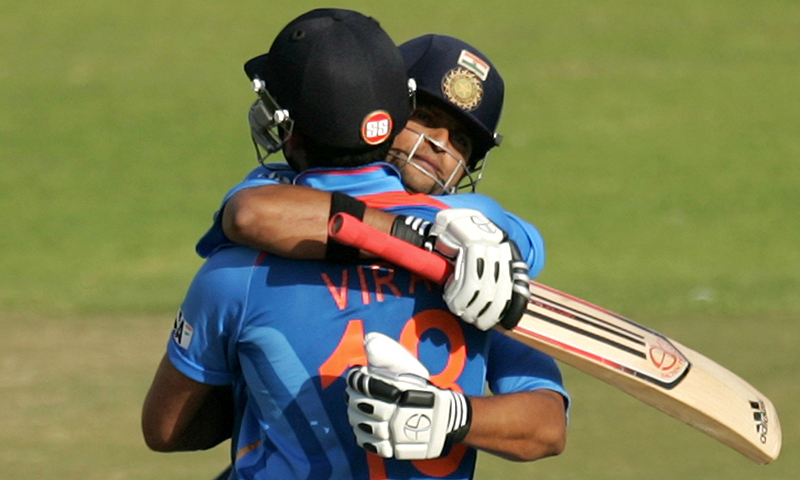 India captain Virat Kohli (L) and his teammate Suresh Raina (R) hug after their victory. -Photo by AFP