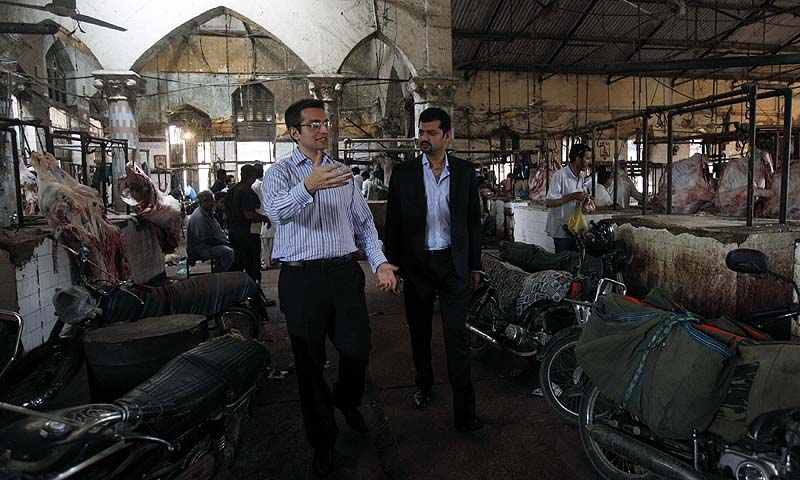 Isfandiyar Shaheen (L) and Shaharyar Ahmed, Principals and Co-Heads of Growth Equity for Cyan Capital, talk during their visit at Karachi's Empress Market August 1, 2013. — Photo by Reuters