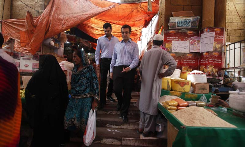Isfandiyar Shaheen (R) and Shaharyar Ahmed, Principals and Co-Heads of Growth Equity for Cyan Capital, talk during their visit at Karachi's Empress Market August 1, 2013. — Photo by Reuters
