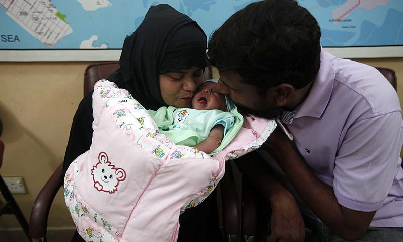 A childless couple kisses their newly adopted daughter, Fatima, whom Pakistani television talk show host Aamir Liaquat Hussain gave them on his show, as they sit at the Chhipa Welfare Association office in Karachi August 1, 2013.   — Photo by Reuters