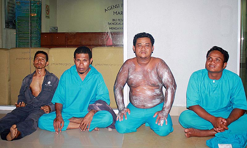 A handout photo taken on August 2, 2013 and received on August 3 from the Malaysian Maritime Enforcement Agency shows passengers who were rescued from an overturned boat sitting at the Maritime office in Tanjung Sedili, Johor, southern Malaysia. Forty Indonesians believed to be illegal immigrants seeking to return home went missing after a boat carrying them sank off the coast of Malaysia, a maritime official said on August 3.— Photo by AFP