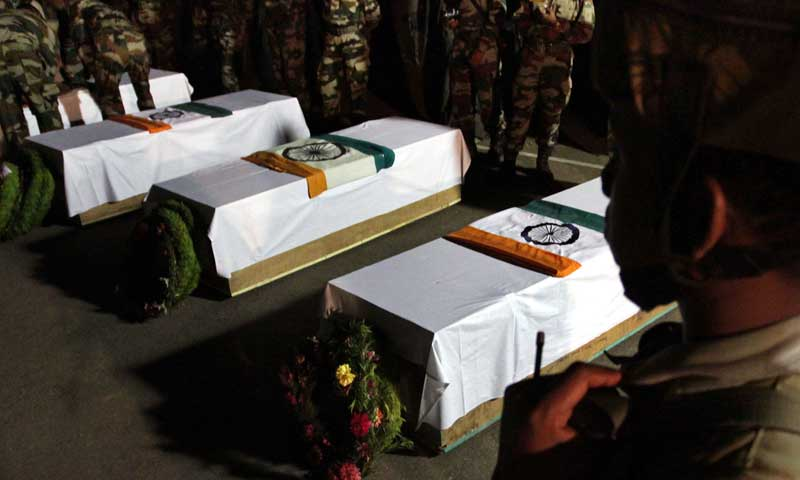 Indian army personnel stand near the coffins of Indian soldiers, who were killed during an ambush, at Brigade headquarters in Poonch, about 240 kilometres from Jammu on August 6, 2013. — Photo by AFP