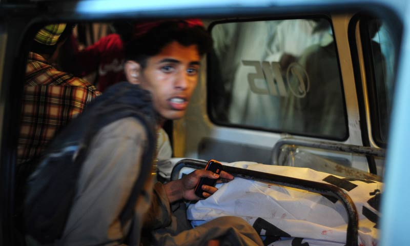 A young boy sits next to the body of a blast victim in an ambulance in Karachi . -AFP Photo