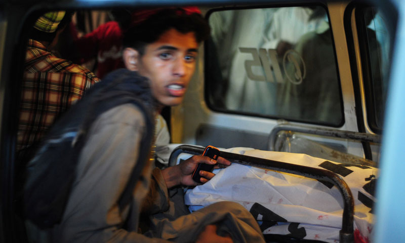 A young Pakistani sits next to the body of a blast victim in an ambulance in Karachi early on August 7, 2013. – AFP Photo