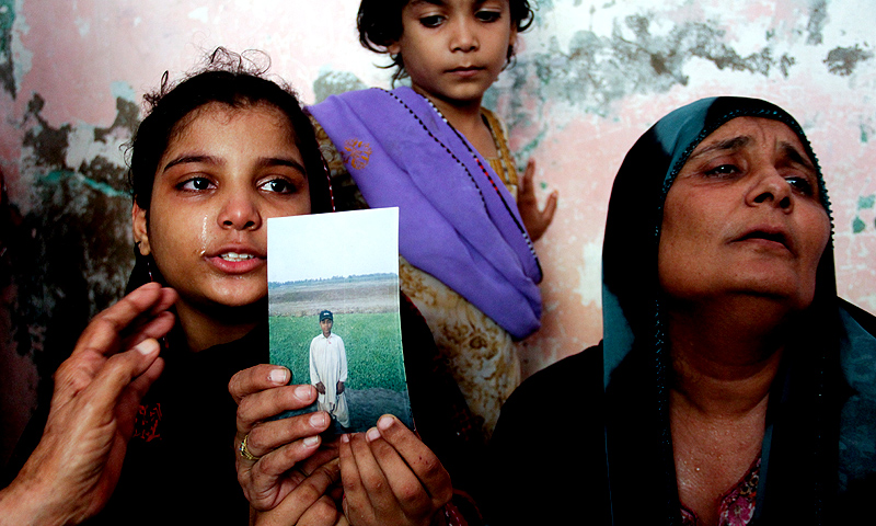The mother and sister of Abdul Basit, one of the blast victims, show his picture. -Photo by Hussain Afzal/ White Star