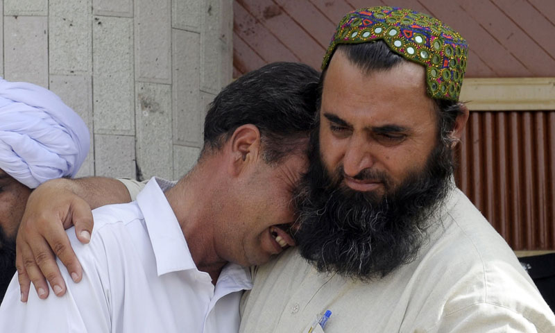 A man comforts a mourner at the site of the suicide bomb attack in Quetta on August 8, 2013. —AFP Photo