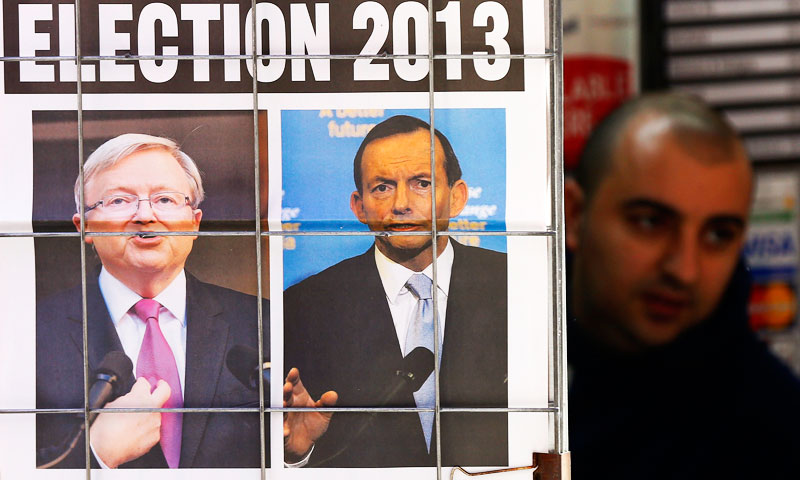 A man walks behind an advertisement of a newspaper with pictures of Australian Prime Minister Kevin Rudd (L) and Opposition Leader Tony Abbott in central Sydney in this August 5, 2013 file photo. - Photo by Reuters