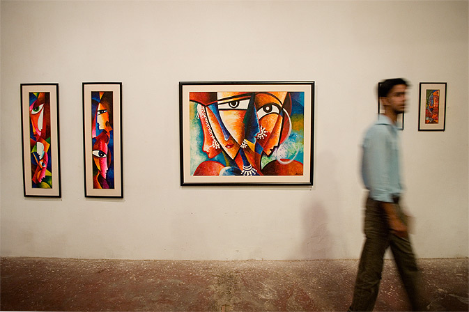 A visitor walks by the vibrant paintings of Haroon Ahmed at The Asahi art exhibition at the Commune Artists Colony. — Photo by Nadir Siddiqui/Dawn.com