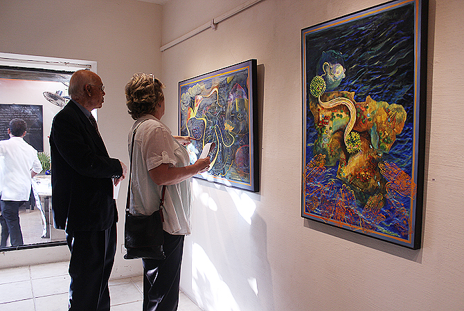 Visitors admire artwork displayed at Koel Gallery by Artist Sabina Zeba Haque. — Photo by Shameen Khan/Dawn.com