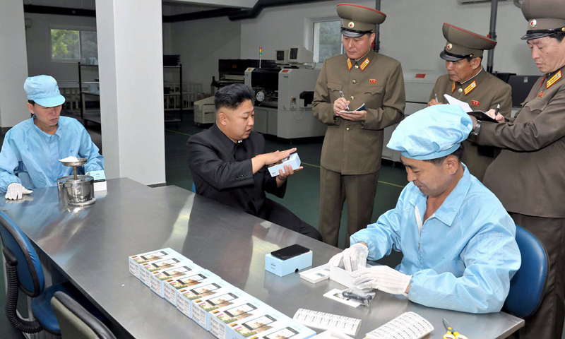 "This undated file picture released by North Korea's official Korean Central News Agency on August 11, 2013 shows North Korean leader Kim Jong-Un inspecting the production process of the new touch-screen mobile phone ""Arirang"" at the May 11 factory at an undisclosed location in North Korea. — AFP Photo"