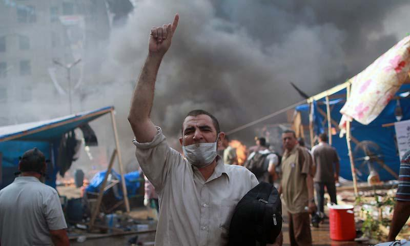 A supporter of the Muslim Brotherhood and Egypt's ousted president Mohamed Morsi gestures during clashes with police in Cairo on August 14, 2013, as security forces backed by bulldozers moved in on two huge pro-Morsi protest camps, launching a long-threatened crackdown that left dozens dead. — Photo by AFP