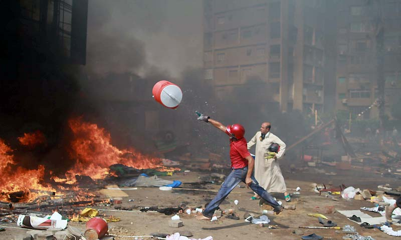 A supporter of the Muslim Brotherhood and Egypt's ousted president Mohamed Morsi throws a water container onto a fire during clashes with police in Cairo on August 14, 2013, as security forces backed by bulldozers moved in on two huge pro-Morsi protest camps, launching a long-threatened crackdown that left dozens dead. — Photo by AFP