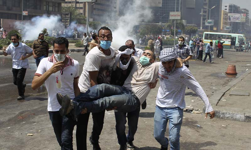 Supporters of deposed Egyptian President Mohamed Mursi carry a protester injured during clashes with riot police and army at around the area of Rabaa Adawiya square, where they are camping, in Cairo August 14, 2013. — Photo by Reuters
