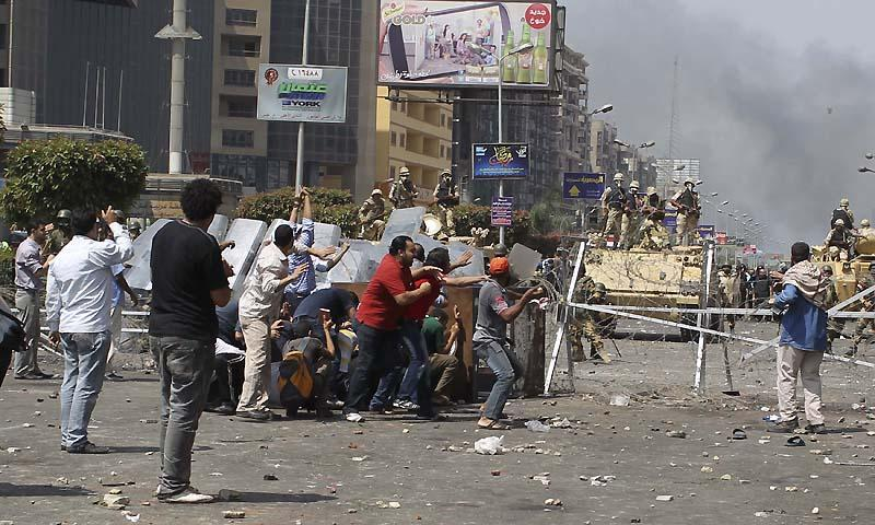 Members of the Muslim Brotherhood and supporters of ousted Egyptian President Mohamed Mursi throw stones at riot police and the army during clashes around the area of Rabaa Adawiya square, where they are camping, in Cairo August 14, 2013. — Photo by Reuters