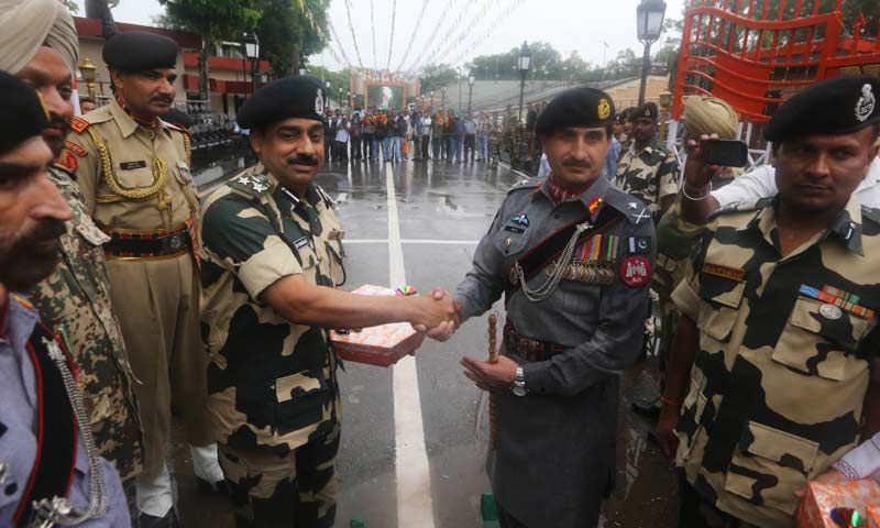 Pakistan troops, right, give sweet to their Indian counterparts on the occasion of Pakistan's Independence Day at Wagah border. -AP Photo