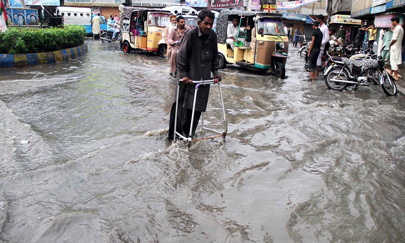 A disabled man crossing the inundated road during heavy rain in the city. — Online photo