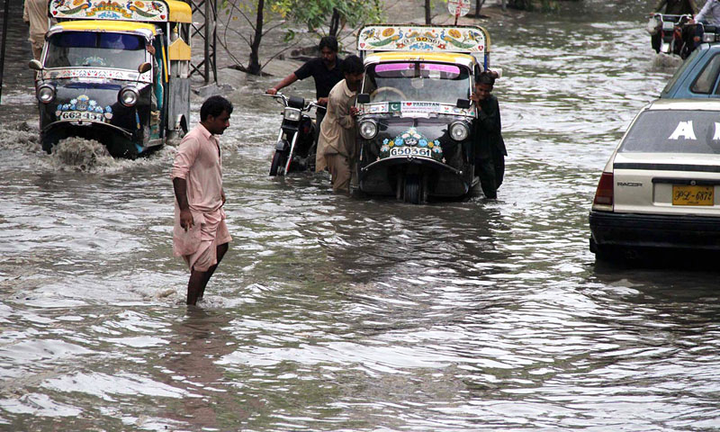 Citizens facing hardships due to water inundated on the road after heavy rain in the city. — Online photo