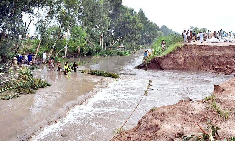 Rescue staffers struggling to repair the damaged protective wall of a canal broken due to flash floods at Jhang-Faisalabad Bypass Road. — Photo by APP