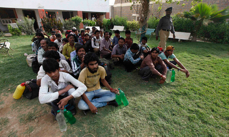 Fishermen from India sit while waiting in line before their release at a prison in Karachi. — File photo/Reuters