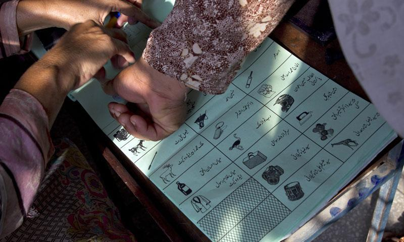 A Pakistani election worker helps a woman to place her thumb print on a ballot paper during elections in Islamabad, Pakistan, Thursday, Aug. 22, 2013. – AP Photo