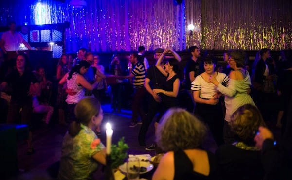 People dance during a Swing night in the hall of Claerchens Ballhaus on July 10, 2013 in Berlin. — Photo by AFP
