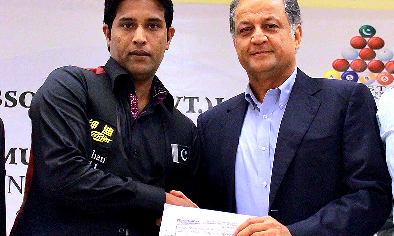 Nadeem Omar, director of Omar Associates, presents a check of two million rupees to Pakistan's world amateur snooker champion Mohammad Asif in Karachi. -Photo by APP