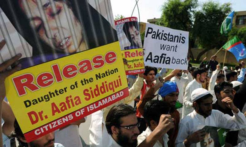 Pakistani activists of the hard-line party Jamaat-i-Islami (JI) carry photographs of Pakistani scientist Aafia Siddiqui as they shout slogans while they march toward the US embassy during an anti-US protest in Islamabad. – AFP Photo/File
